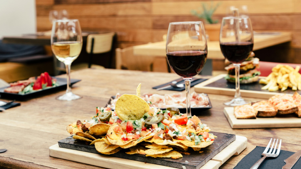 This is a stock image of a dinner table with a few plates of nachos, 2 glasses of wine and 1 glass of chardonnay