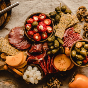 This is a display of a fall charcuterie board. Stuffed Peppadew Peppers, Persimmons, pickles and meats adorn a wooden board.